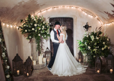 Bride and Groom in Chapel Porchway surrounded by flowers and rustic lanterns.