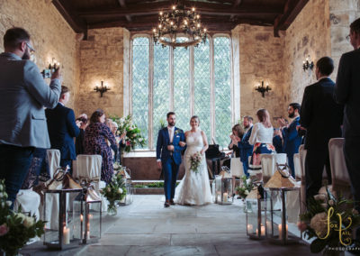 A ceremony in the Chapel with bride and groom in front of large windows.