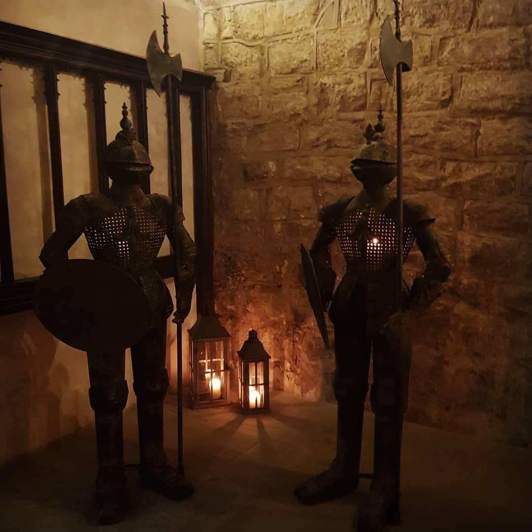 Two metal knights with candles in their armour and lanterns behind them.
